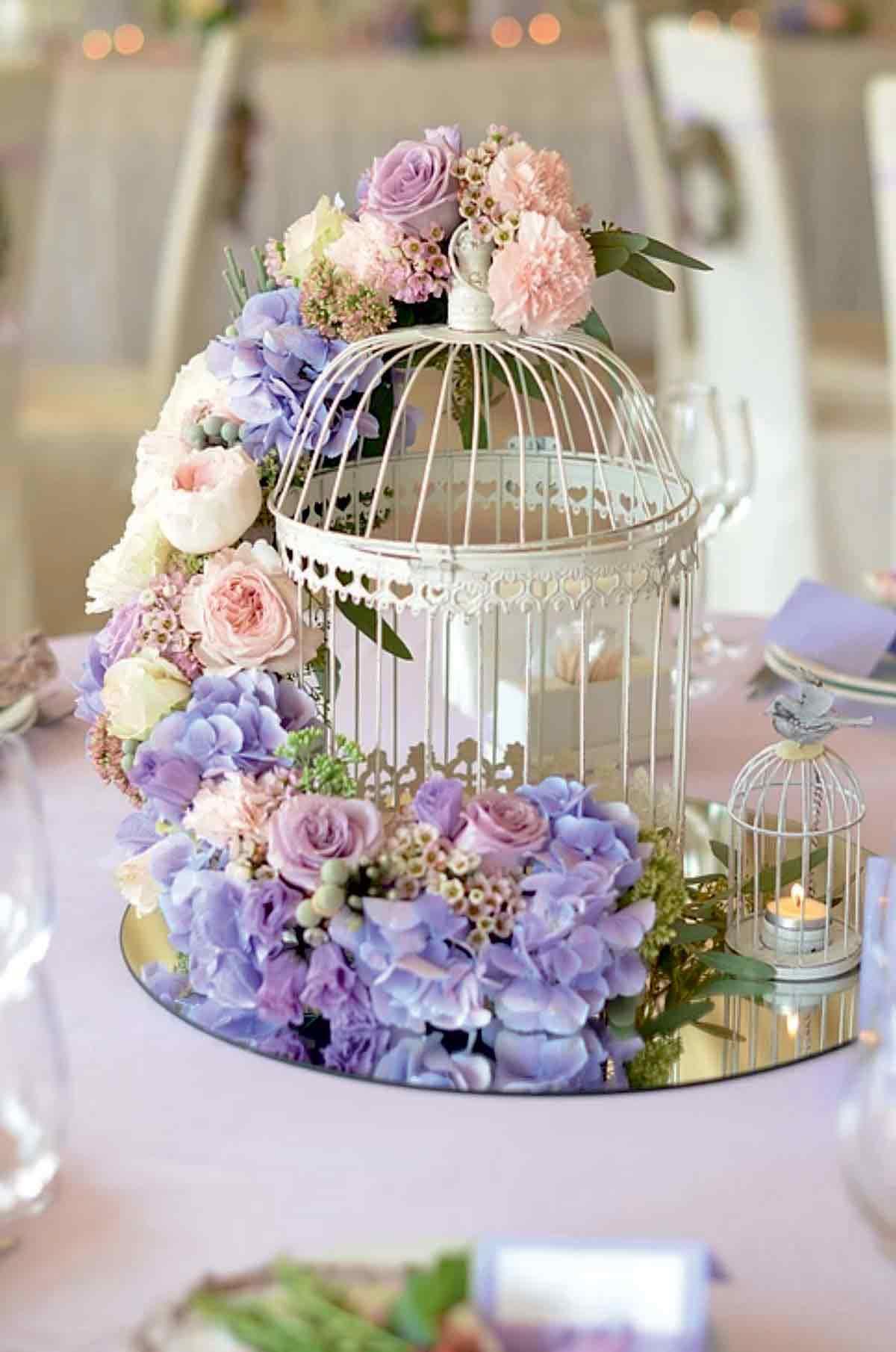 Bouquet violet et blanc avec cage d'oiseau sur une table